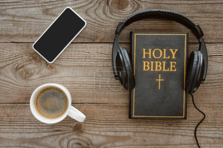 top view of holy bible with headphones, smartphone and coffee on wooden tabletop