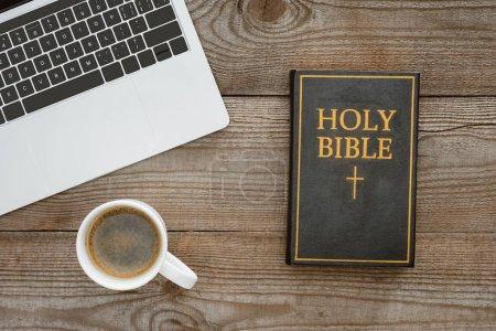 Photo pour Vue de dessus de Sainte bible avec ordinateur portable et café sur la table en bois - image libre de droit
