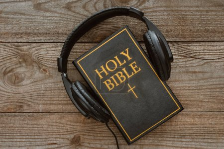 top view of holy bible with headphones on wooden tabletop