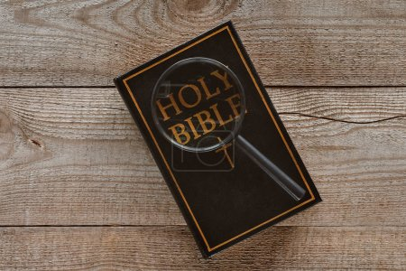 Photo for Top view of holy bible with magnifying glass on wooden table - Royalty Free Image