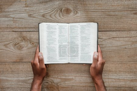 Photo for Cropped shot of man holding holy bible over wooden table - Royalty Free Image