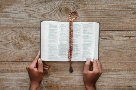 Photo pour Recadrée tir d'afro-américain de lire la Sainte bible avec perles située plus haut sur la table en bois - image libre de droit