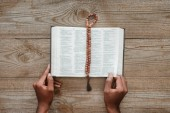 cropped shot of african american man reading holy bible with beads lying above on wooden table