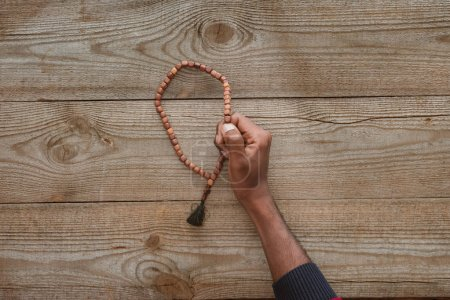 cropped shot of african american man holding beads on wooden table