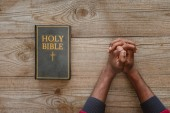 cropped shot of african american man sitting at rustic wooden table with holy bible