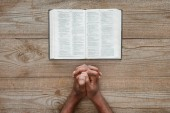"""Постер, картина, фотообои """"обрезанное выстрел афро-американских человек молится с Библии на деревенский деревянный столик"""""""