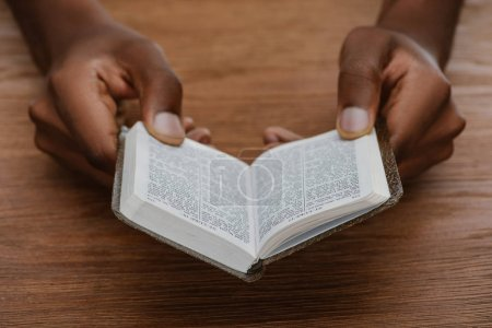 cropped shot of african american man reading holy bible on wooden table