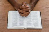 """Постер, картина, фотообои """"обрезанное выстрел афро-американских человек молится с Библии на деревянные поверхности"""""""
