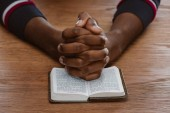 cropped shot of african american man praying with holy bible