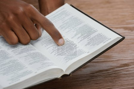 cropped shot of african american man reading holy bible and pointing at psalm