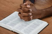 cropped shot of african american man praying with holy bible on wooden table