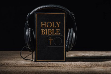 close-up shot of holy bible with headphones standing on wooden table isolated on black