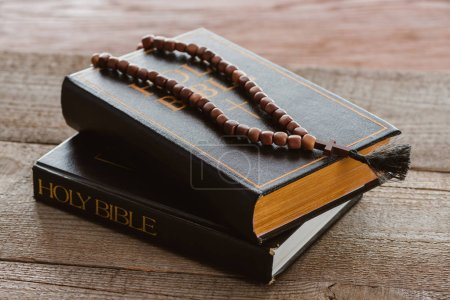 Photo for Close-up shot of stacked bible books with beads on wooden surface - Royalty Free Image