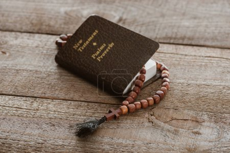 close-up shot of new testament book with beads on wooden surface