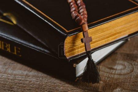Photo pour Gros plan tiré d'empilés Saintes bibles avec des perles sur la table en bois - image libre de droit