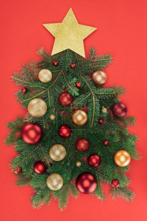 top view of pine tree branches, golden star and christmas balls arranged in christmas tree isolated on red