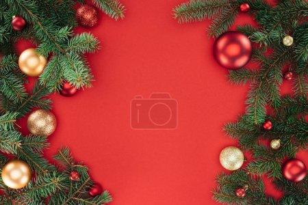 Photo pour Pose plate avec des branches de pin avec des boules de Noël rouges et dorées isolées sur rouge - image libre de droit