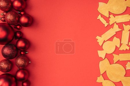 flat lay with red christmas toys and decorative wooden candies isolated on red