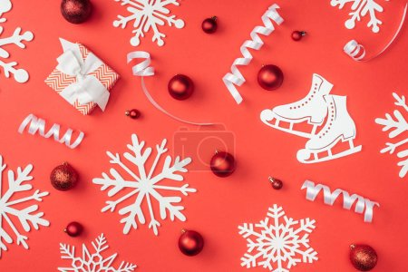 flat lay with white decorative snowflakes, ribbons, red christmas toys and wrapped gift isolated on red
