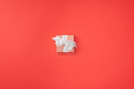 Photo for Top view of wrapped christmas gift with white ribbon isolated on red - Royalty Free Image