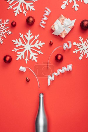 Photo for Top view of present, silver bottle, red christmas toys, white ribbons and decorative snowflakes arranged isolated on red - Royalty Free Image