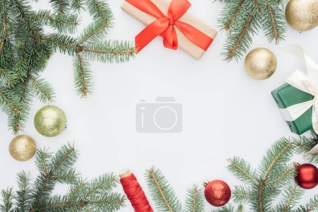 flat lay with arranged pine tree branches, gifts and christmas toys isolated on white