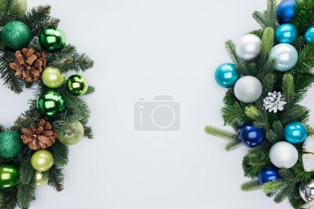 top view of pine tree wreathes with green, blue and silver christmas balls isolated on white