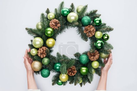 cropped shot of woman holding christmas wreath with green toys isolated on white