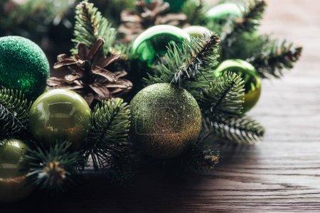 Photo pour Bouchent la vue de la Couronne d'arbre de pin avec des boules de Noël vert sur fond en bois - image libre de droit