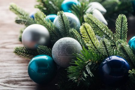 close up view of pine tree wreath with blue and silver christmas toys on wooden background