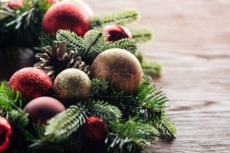Photo pour Vue rapprochée de couronne de pins avec des boules de Noël rouges et dorées sur fond en bois - image libre de droit