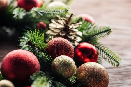 close up view of pine tree wreath with red and golden christmas balls on wooden background