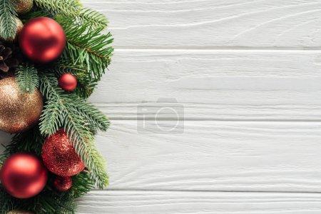 Photo pour Vue de dessus de la couronne avec des jouets de Noël rouges sur la surface en bois blanc - image libre de droit