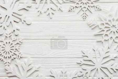 Photo for Flat lay with decorative snowflakes on white wooden tabletop with blank space in middle - Royalty Free Image