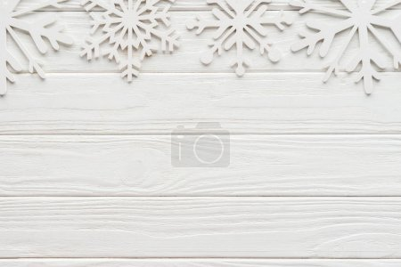 Photo for Flat lay with decorative snowflakes on white wooden tabletop - Royalty Free Image