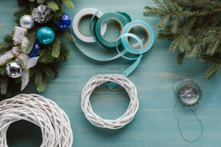 top view of arranged decorations for handmade christmas wreath on blue wooden tabletop