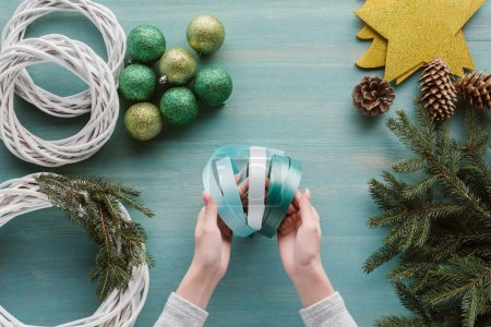 partial view of woman holding ribbons for handmade christmas wreath decoration on blue wooden tabletop