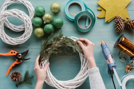 partial view of woman making handmade christmas wreath on blue wooden surface