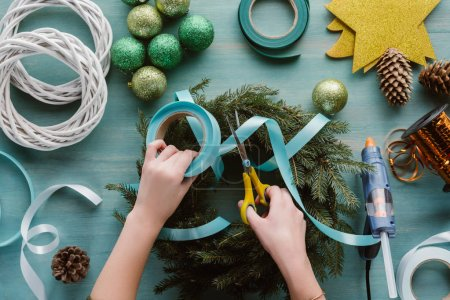 cropped shot of woman decorating handmade christmas wreath with blue ribbon on blue wooden tabletop
