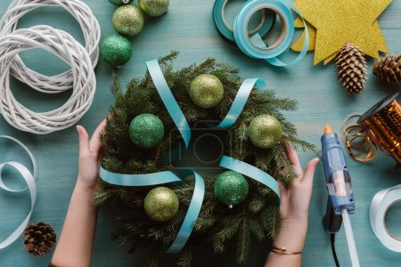 cropped shot of woman with handmade christmas wreath decorated with ribbon and toys on blue wooden surface