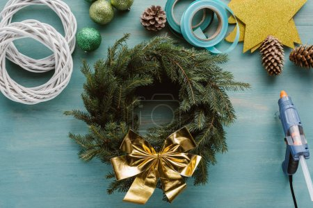 top view of arranged pine tree branches, decorations for handmade christmas wreath on blue wooden tabletop