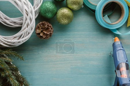 top view of glue gun and decorations for handmade christmas wreath on blue wooden surface