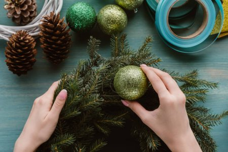 partial view of woman decorating handmade pine tree wreath with christmas toys on blue wooden surface