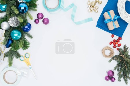 top view of handmade christmas wreath decorations and scissors isolated on white
