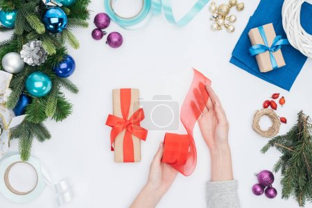 partial view of  woman holding red ribbon for christmas present decoration isolated on white