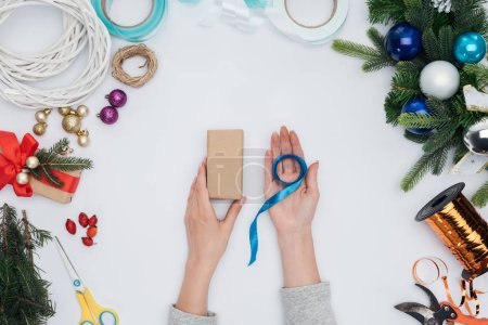 partial view of woman holding blue ribbon and wrapped christmas gift in hands isolated on white