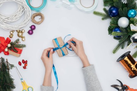cropped shot of woman wrapping christmas gift with blue ribbon isolated on white