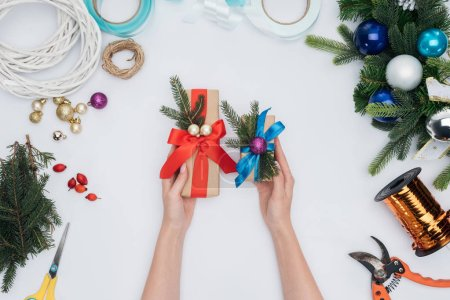 partial view of woman holding wrapped christmas gifts in hands isolated on white
