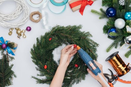 cropped shot of woman decorating handmade christmas wreath with briar berries isolated on white