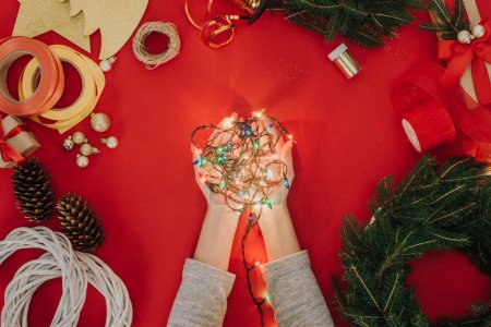 Photo for Cropped shot of woman holding christmas lights in hands with pine tree branches and decorations for handmade wreath on red backdrop - Royalty Free Image